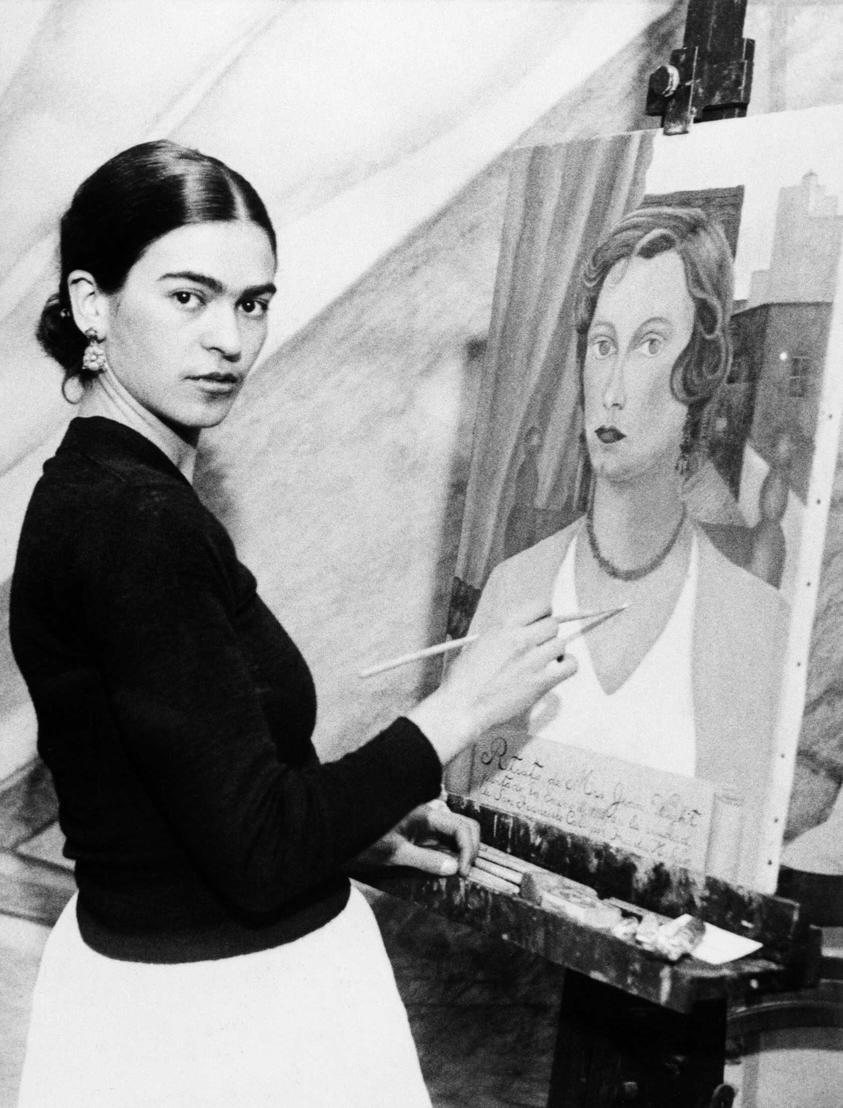 Original Caption: 1/22/1931- Even though her famous husband sits by and declines to comment on her art ambitions, Mrs. Diego Rivera, wife of the famous Mexican artist, can and does, do very passable portraits. Photo shows Mrs. Diego Rivera painting one now, and she is doing a mural for the San Francisco Stock Exchange, with one of her portraits of a San Francisco society woman.